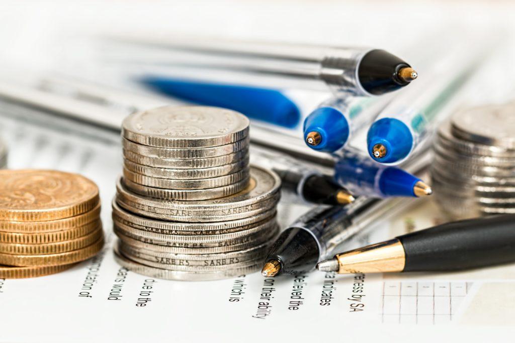 coins beside ballpoint pens